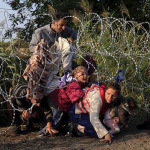 Rifugiati siriani attraversano una recinzione mentre entrano in Ungheria al confine con la Serbia, vicino a Roszke, 27 agosto 2015. Credito: Bernadett Szabo / Reuters