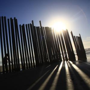 Le persone si trovano di fronte un muro che separa il Messico dagli Stati Uniti a Tijuana come fotografato a Imperial Beach, California, 5 novembre 2010. Credito: Eric Thayer / Reuters