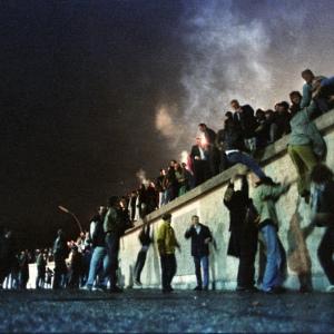 I cittadini della Germania Est si arrampicano al muro di Berlino alla Porta di Brandeburgo dopo l'apertura del confine, che venne annunciato nelle prime ore del 9 novembre 1989. Credit: Herbert Knosowski/Reuters