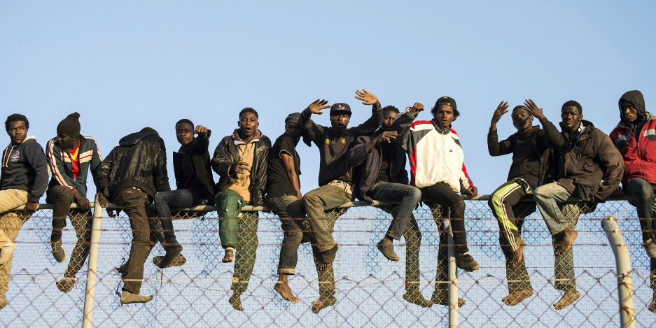Migranti africani siedono in cima ad una recinzione di confine durante un tentativo di attraversare territori spagnoli, tra Marocco e l'enclave nord africana di Melilla, il 22 ottobre 2014. Credit: Jesus Blasco de Avellaneda /Reuters
