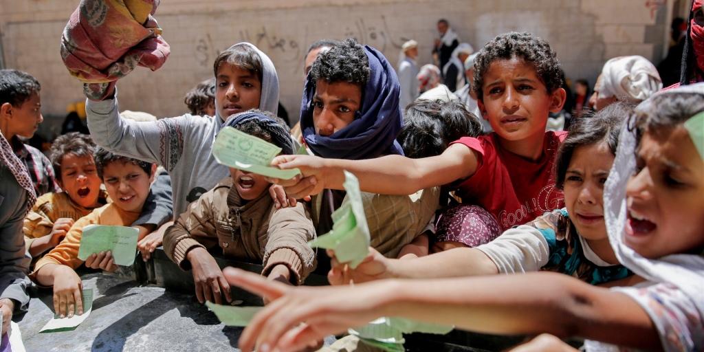Yemeniti che presentano i documenti per ricevere le razioni alimentari che vengono fornite dalla caritas locale a Sana, la capitale. Hani Mohammed/Associated Press