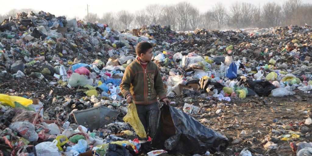 Bambino kosovaro che rovista nella spazzatura per cercare vestiti e avanzi di cibo.